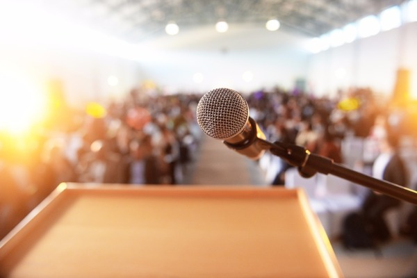 microphone-in-front-of-podium-with-crowd-in-the-background-picture-id614138202